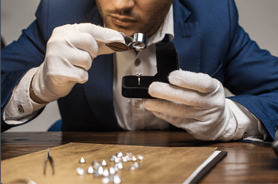Jewelry appraiser examining jewelry ring with magnifying glass